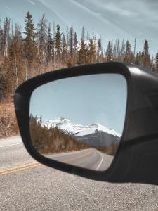 A beautiful reflection of a mountain in a side mirror of a car